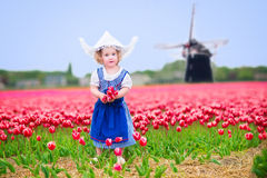 Cheerful girl in tulips field with windmill in Dutch costume. Adorable curly toddler girl wearing Dutch traditional national costume dress and hat playing in a Royalty Free Stock Photography