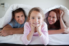 Cheerful girl under bed cover with parents Royalty Free Stock Images
