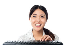 Cheerful girl using computer keyboard to type Royalty Free Stock Photos
