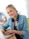 Cheerful girl using laptop and headphones stock images