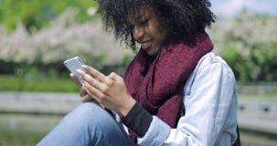 Cheerful girl using smartphone stock video footage