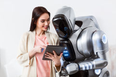 Cheerful girl using tablet. See how it works. Cheerful delighted beautiful girl holding tablet and showing it to the robot while expressing gladness royalty free stock photos