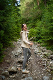 Cheerful girl walking through forest path, looking back smiling Stock Photo