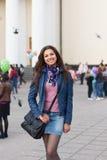 Cheerful girl walking through street Royalty Free Stock Photos