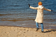Cheerful girl walks on beach in solar autumn day Stock Photo