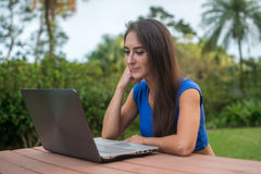 Cheerful girl watching online video on laptop computer sitting in the park Stock Photos