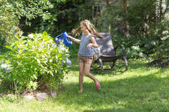Cheerful girl watering flowers Royalty Free Stock Photos
