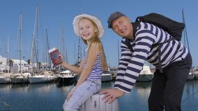 Cheerful girl waving hand and riding on suitcase together father in sea port. Dad with daughter sitting on travel suitcase in sea port on yachts background stock footage