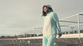 Cheerful girl is wearing blue kigurumi of unicorn and jumping on beach. Joyful young woman is jumping on a pebble beach. She is dancing in kigurumi costume of stock footage