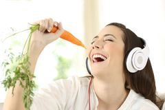 Girl singing using a carrot as a microphone. Cheerful girl wearing headphones singing using a carrot as a microphone at home Royalty Free Stock Image