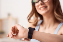 Cheerful girl wearing her wrist watch stock photos