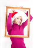 cheerful girl wearing santa hat inside the frame Royalty Free Stock Photos