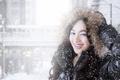 Cheerful girl wearing winter coat in snowy day Royalty Free Stock Photo