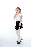 Cheerful girl in a white blouse, black skirt and her mother's shoes Royalty Free Stock Photos