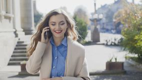 Cheerful girl in a white coat goes and speaks on a smartphone stock video footage