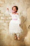 Cheerful girl in a white dress mulatta jump Royalty Free Stock Image