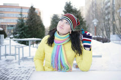 Cheerful girl in winter. Cheerful girl winter sitting in a street cafe and twirled his finger hair Royalty Free Stock Photos