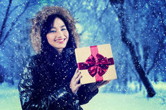 Cheerful girl with winter clothes holding gift. Image of cheerful teenage girl holding a gift box while smiling happy and wearing winter jacket, shot outdoors Stock Photography