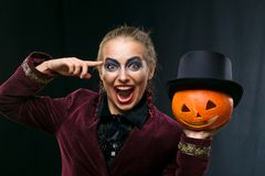 Cheerful girl witch on Halloween with pumpkin. stock photo