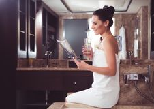 Cheerful girl wrapped in towel holding magazine in spa royalty free stock photo