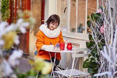 Cheerful girl writing Christmas cards in cafe Royalty Free Stock Images