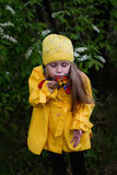 Cheerful girl in a yellow raincoat blows a butterfly which sits on a hand on a spring day in the park Stock Image