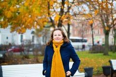 Cheerful girl in yellow scarf enjoying fall day Stock Photo