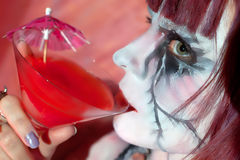 Cheerful girl zombie with glass of red drink Stock Images