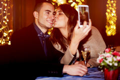 Cheerful girlfriend kissing her boyfriend on the cheek while taking self portrait Royalty Free Stock Photo