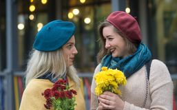 Cheerful girlfriends, with bouquets of flowers. royalty free stock image