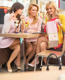 Cheerful girlfriends eating fruit ice-cream Stock Image