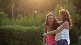 Cheerful girlfriends hugging in park. Cheerful friends walking in a summer park. Girls hugging each other. The concept of true friendship stock footage