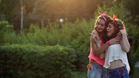 Cheerful girlfriends hugging in park. Cheerful girlfriend walking in a summer park. Girls hugging each other. Friends looking to the side. The concept of true stock video