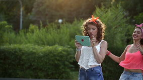 Cheerful girlfriends meet in park. stock footage