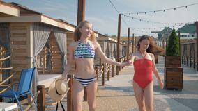 Cheerful girlfriends with slim bodies in swimsuits run holding hands during summer vacation in luxurious resort