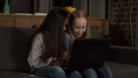 Cheerful girlfriends watching cartoons on laptop stock footage