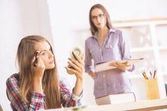 Cheerful girls applying makeup Stock Photography