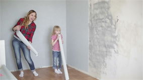 Cheerful girls are dancing and singing near the wall with rolls of wallpaper in their hands. Happy funny family is fooling around. Pregnant woman and her stock video footage