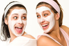 Cheerful girls having facial mask and laughing. At each other Stock Image