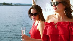 Cheerful girls having party on deck of sailboat. Happy women in red clothes and sun glasses tasting wine at sailboat party during river trip. Buddies enjoying stock footage