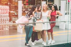 Cheerful girls are looking at each other and smiling. They are standing at the edge of glass cover. Girls are spending. Time together Stock Photos