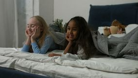 Cheerful girls looking out under the blanket. Joyful multiracial preteen girls looking out under the blanket in bedroom and smiling. Portrait of excited little stock footage
