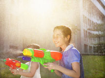 Cheerful girls playing water guns in the park Stock Image