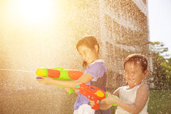 Cheerful girls playing water guns in the park Stock Photos