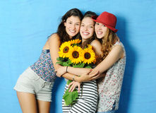 Cheerful girls. Portrait of beautiful girls with sunflowers on blue background Stock Image