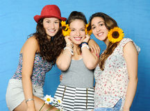 Cheerful girls. Portrait of beautiful girls with sunflowers on blue background Stock Photo