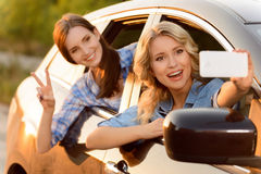 Cheerful girls sitting in the car. Say cheese. Vivacious delighted young friends driving in the car and making photos while reveling in it Stock Photos