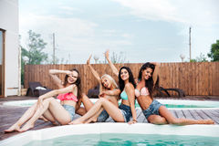 Cheerful girls sitting and relaxing near swimming pool Royalty Free Stock Photos