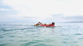 Cheerful girls swimming on inflatable mattress in sea. Cheerful teenager swimming on inflatable mattress in sea in cloudy weather. Girl enjoying bathing in blue stock video footage