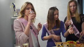 Cheerful girls take food at a buffet table. They drink champagne. stock video footage